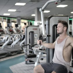 man-in-white-tank-top-and-grey-shorts-sitting-on-exercise-3838926
